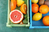 Fresh citrus fruits with green leaves in wooden box on color wooden background — ストック写真