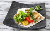 Veggie wrap filled with chicken and fresh vegetables on wooden table — Stock Photo