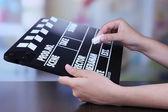 Black cinema clapper board in hands — Stok fotoğraf
