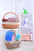 Colorful towels and clothes in baskets on table — Stock Photo