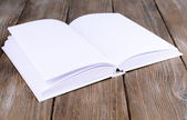 Open white book on wooden table, close-up — Stock Photo