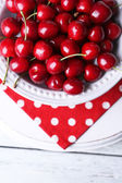 Sweet cherries on plate on wooden background — Stock Photo