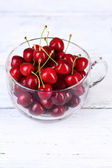Sweet cherries in glass mug on wooden background — Stock Photo