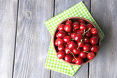 Sweet cherries in color bowl on wooden background — Stockfoto