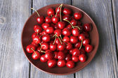 Sweet cherries  on plate on wooden background — Zdjęcie stockowe
