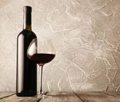 Bottle of red wine with glass — Stock fotografie
