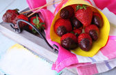 Strawberry in chocolate on skewers in paper bag — Stock Photo
