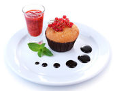 Tasty muffin with chocolate and red currant sauces on plate isolated on white — Stock Photo