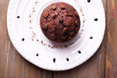 Chocolate muffin on plate wooden background — Stok fotoğraf