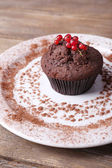 Chocolate muffin with red currant on plate on wooden background — Stock Photo