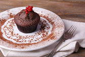Chocolate muffin with red currant on plate on wooden background — Stockfoto