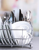 Clean dishes drying on metal dish rack on light background — Stock Photo