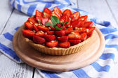 Strawberry tart on wooden tray, on color wooden background — Stock fotografie