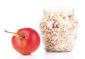 Homemade granola in glass jar and fresh apple, isolated on white — Stock Photo
