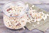 Homemade granola in glass jar, on color wooden background — Foto Stock