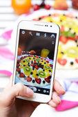 Hand att göra foto av frukt pizza på mobiltelefon — Stockfoto