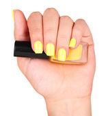 Female hand with stylish colorful nails holding bottle with nail polish — Stock Photo