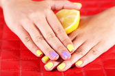 Female hand with stylish colorful nails holding fresh lemon — Stock fotografie