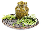 Fresh  and canned peas in glass jar on wicker mat, isolated on white — Stock Photo