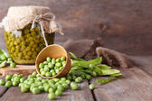 Fresh  and canned peas in bowl and glass jar on napkin, on wooden background — Zdjęcie stockowe