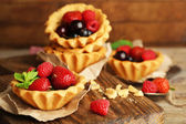 Tasty tartlets with berries on wooden table — Stock Photo