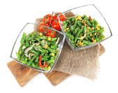 Salad with green beans, ham and  corn in glass bowls, on wooden board, isolated on white — 图库照片