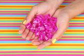 Female hand with stylish colorful nails holding decorative stones — Stock Photo
