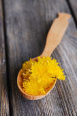 Dandelions in wooden spoon on table close-up — Stock Photo