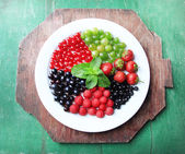 Forest berries on plate, on color wooden background — Zdjęcie stockowe