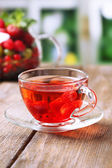 Fruit red tea with wild berries in glass cup, on wooden table, on bright background — Stock Photo