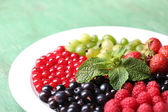 Forest berries on plate, on color wooden background — Foto Stock