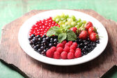 Forest berries on plate, on color wooden background — Stock Photo