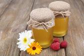 瓶がいっぱいのおいしい新鮮な蜂蜜、木製テーブルの上の野生の花 — ストック写真
