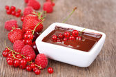 Ripe sweet berries and liquid chocolate on wooden table — Stock Photo