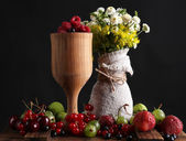 Still life with berries and flowers on dark background — Stock Photo
