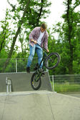 Boy jumping with his BMX Bike — Stock Photo