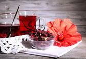 Hibiscus tea in glass teapot and flower on color napkin on wooden background — Stock Photo