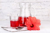 Cold hibiscus tea in glass jug with hibiscus flower on wooden background — Stock Photo