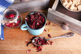 Dried hibiscus tea in color mug, brown sugar  in box on wooden background — Stock Photo