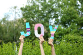 Hands holding up letters building word Joy on natural background — Stock Photo