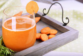 Glass of carrot juice and fresh carrots on wooden tray on table close up — Stock Photo