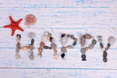 Word happy made from sea shells and stones on wooden background — Stock Photo