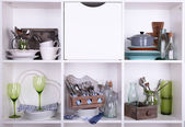 Kitchen utensils and tableware on beautiful white shelves — Stock fotografie