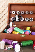 Colorful threads for needlework in wooden box on shelf in room — Stock Photo