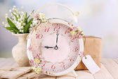 Beautiful vintage alarm clock with flowers on light background — Foto de Stock