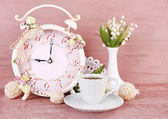 Beautiful vintage alarm clock with flowers and cup of tea on pink wooden background — Stock Photo