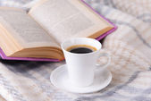 Cup of coffee on plaid with book — ストック写真
