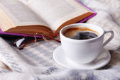 Cup of coffee on plaid with book — Stockfoto