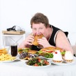 Fat man eating a lot of unhealthy food — Stock Photo #49096307