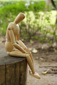 Wooden pose puppet sitting on wooden timber — Zdjęcie stockowe